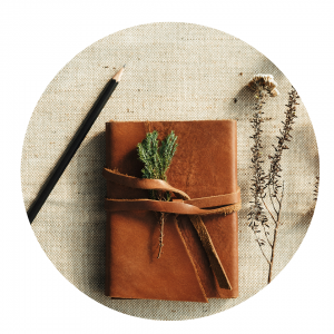 Photo of a brown leather journal with a sprig of herbs tucked into its leather tie on a hessian cloth with a pencil to the left and a sprig of herbs to the right.