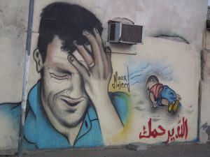 Painting of a man crying next to a dead baby on a beach. Mural by Majeed in Haramel, Oman